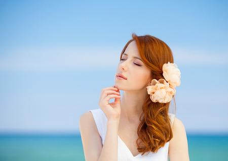 Young redhead girl in white dress and flower in hair have a rest on summertime sea beach