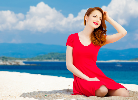 Young redhead girl in red dress have a rest on summertime sea beach