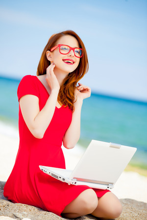 Young redhead girl in red dress and computer have a rest on summertime sea beach
