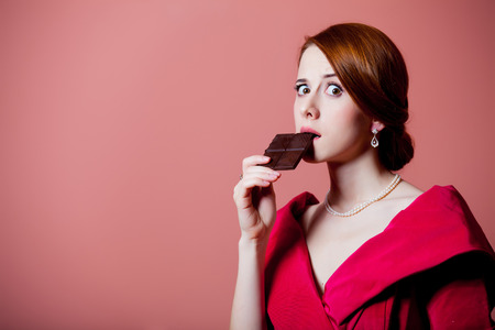 Young surprised woman in red Victorian epoch clothes with chocolate on pink background