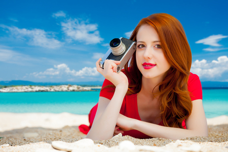 Young redhead girl in red dress with vintage camera have a rest on summertime sea beach