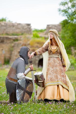 Joven caballero medieval y dama en la hierba verde al aire libre en primavera. Foto de archivo