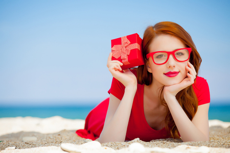 Young redhead girl in red dress with gift box have a rest on summertime sea beach