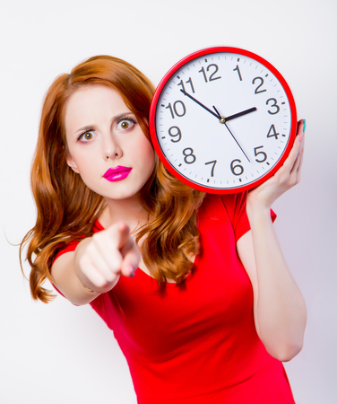 Surprised redhead girl in red dress with big clock on white background