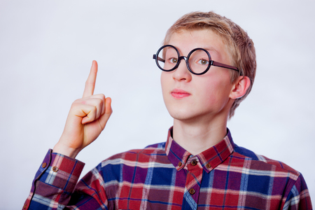 Young nerd teen boy with round glasses on white background