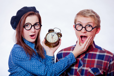 Young nerd couple holding alarm clock on white background