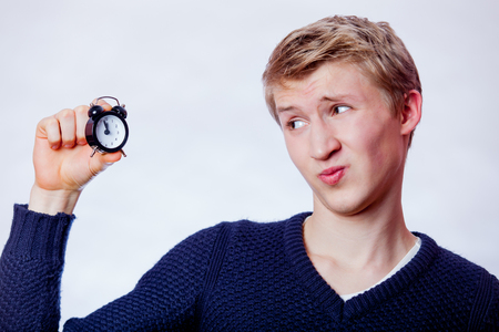 Young teen boy with small alarm clock on grey background