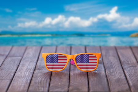 Sunglasses with american flag on wooden table and tropical summer background