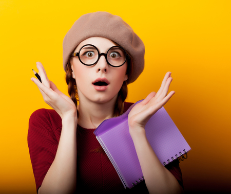 young redhead nerd girl with eyeglasses and beret on yellow background Stock fotó