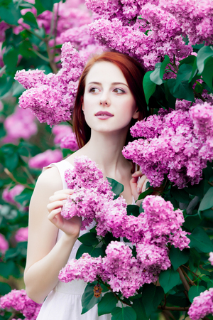 Young redhead girl in white dress in springtime garden of lilac.