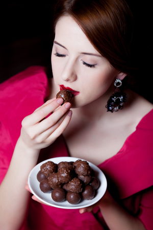 Young surprised woman in red Victorian epoch clothes with chocolate candy on dark background Stock Photo