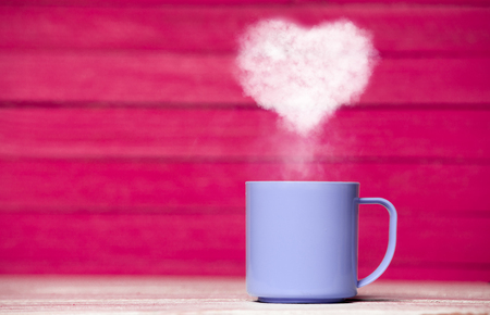 Heart shape steam from a cup of coffee on pink background Stock Photo
