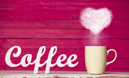 Heart shape steam from a cup of coffee and word Coffee on pink background