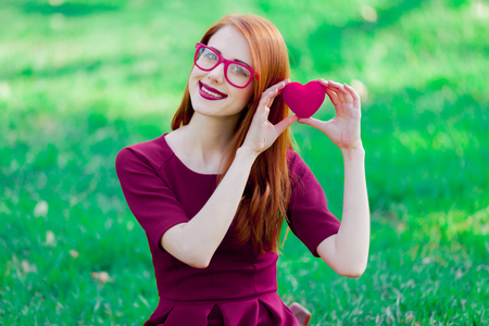 Portrait of a young redhead girl sitting on green grass in springtime