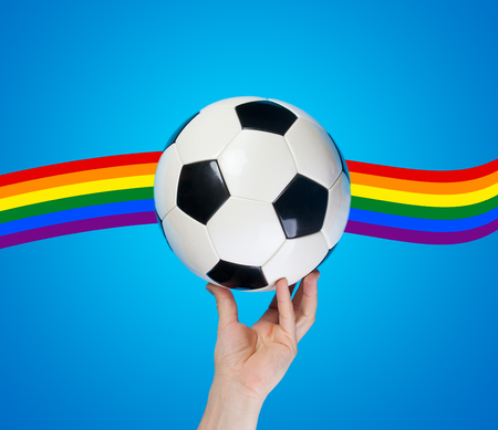 Hand holding football ball on blue background with gay rainbow. Stock Photo
