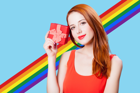 Redhead girl with gif box on blue background with rainbow Stock Photo