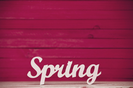 wooden Spring word on pink wooden background