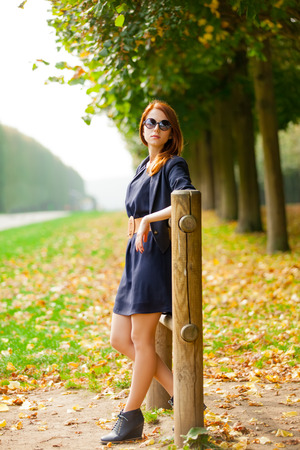 Young beautiful redhead girl in blue dress posing in Garden of Verssailles, France Stock Photo