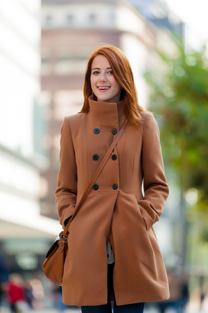Young redhead woman in coat have a rest on Frankfurt streets, Germany Stok Fotoğraf