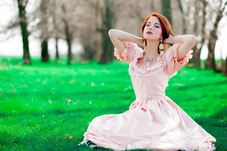 Portrait of a young redheadd girl in victorian style dress sitting on grass in springtime Stockfoto