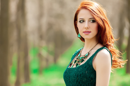 Portrait of a beautiful style redhead girl in green dress in the park Stock fotó