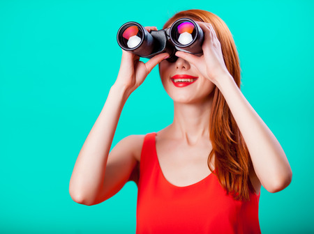 Young redhead girl with binoculars on mint background Foto de archivo