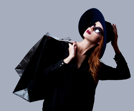 Girl in dark style in sunglasses with shopping bags on grey background
