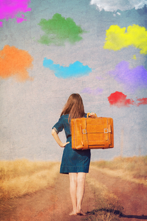 Brunet girl with suitcase walking on the road at countryside in summertime with colorful clouds