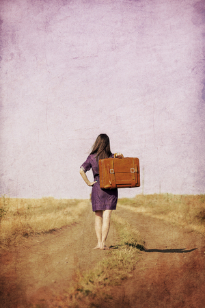 Brunet girl with suitcase walking on the road at countryside in summertime