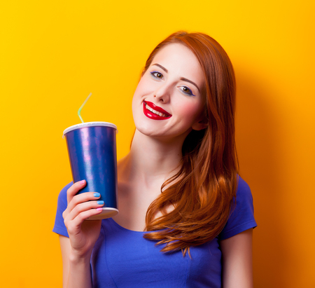 Portrait of a young redhead girl with movie cola on yellow background Stock Photo