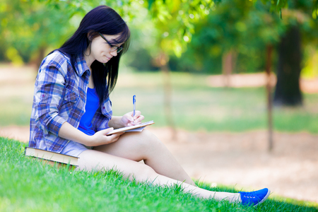 Young brunette student girl with notebooks studying on green grass in summertime