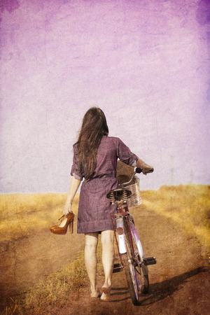 Young brunet girl walking down the road with bike at countryside Stock Photo