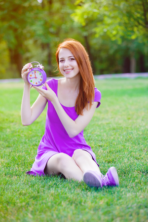 Redhead girl with litle alarm clock in summertime park outdoor