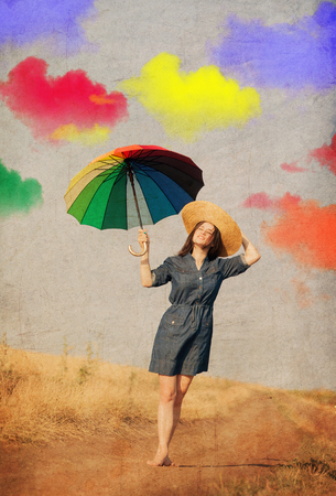 Young brunet girl with colorful umbrella and clouds on background