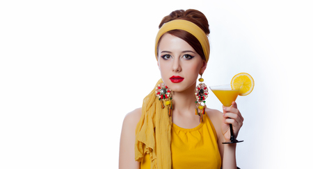 Young redhead girl in 70s clothes style with tropical cocktail on white background