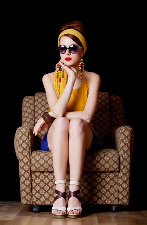 Young redhead girl in 70s clothes style sitting in chair on black background