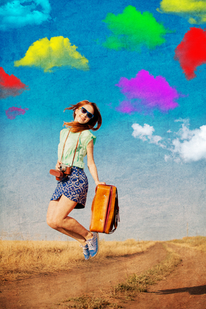Redhead girl with suitcase and colorful clouds on background at countryside. Image in old colro style