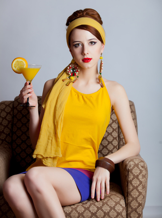 Young redhead girl in 70s clothes style sitting in armchair with cocktail on black background Stock Photo