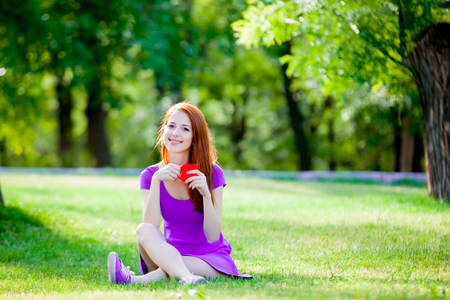 Redhead girl with cup of coffee in summertime park outdoor