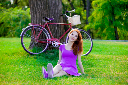 Young redhead girl sitting on grass near vintage bike on background. Summer park location