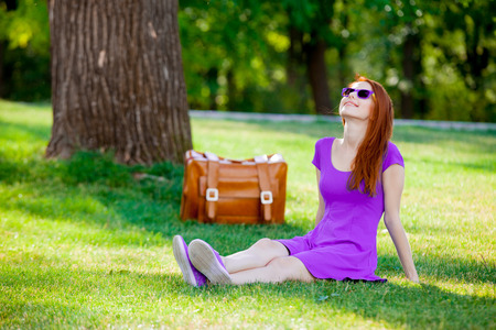 Smily redhead girl in sunglasses with suitcase at summertime park outdoor
