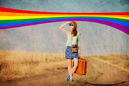 Redhead girl with suitcase and rainbow on background at countryside. Image in old colro style