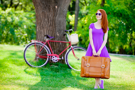 Young redhead girl in sunglasses holding suitcase on bike and green summertime park outdoor Stock Photo
