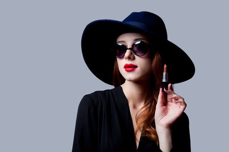 Redhead girl in sunglasses and hat holding lipstick on grey background