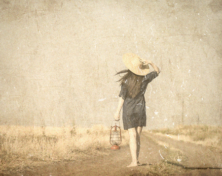 Girl in hat with lamp waking on the contryside road. Image in old color style Stock Photo