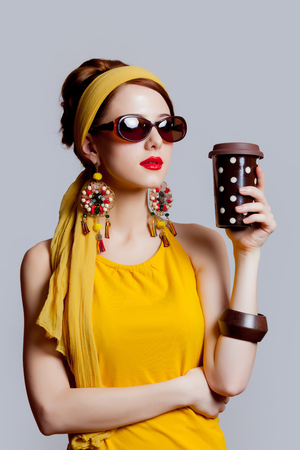 Young redhead girl in 70s clothes style with coffee cup on grey background