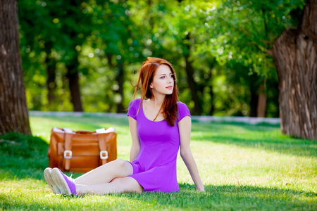 Smily redhead girl with suitcase at summertime park outdoor