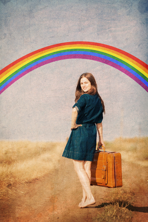 Brunet girl with suitcase walking on the road at countryside in summertime with rainbow on background. Image in old style