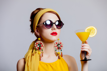 Young redhead girl in 70s clothes style with tropical cocktail on grey background