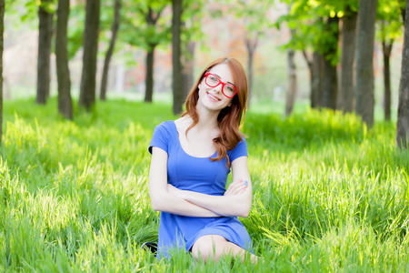 Portrait of a young redhead girl in eyeglasses sitting on green grass in the park